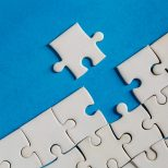 Unfinished red with white jigsaw puzzle pieces on blue background